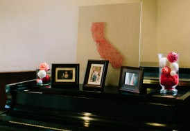 Vases of decorative balls, photos, and a map of where we met on the piano in the reception hall