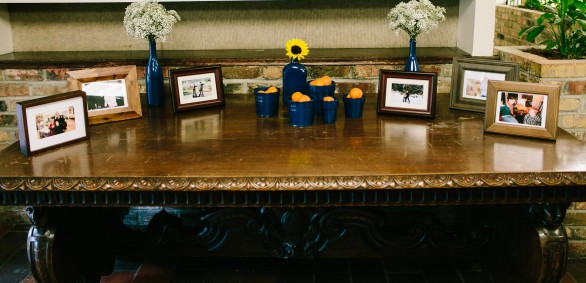 Welcome table with photos, and painted bottles and pots filled with flowers and clementines for guests to enjoy